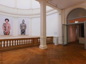 """Vue de l'entrée de l'exposition avec deux portraits de personnes tatouées extraites de la série """"Why I love tattoos"""" de Ralph Mitsch"""