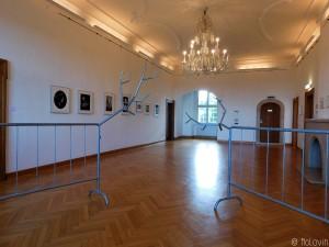 """Grande salle centrale de l'exposition avec les """"barrières"""" Paradise Now 1 + Now 4 de Krištof Kintera et à gauche la série de photos sans titre de Juul Kraijer."""