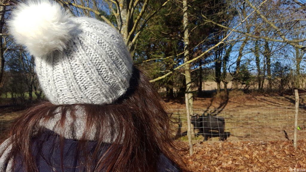 Mon bonnet Chic de Phildar tricoté et moi devant l'enclos des moutons dans mon jardin.