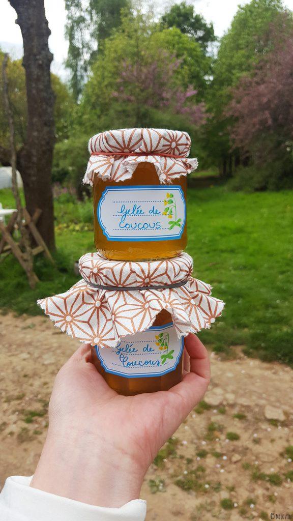 La gelée de fleurs jaunes et comestibles de coucou ou primevère officinale en pots avec étiquettes et cache-pots en chutes de tissus dans le jardin.