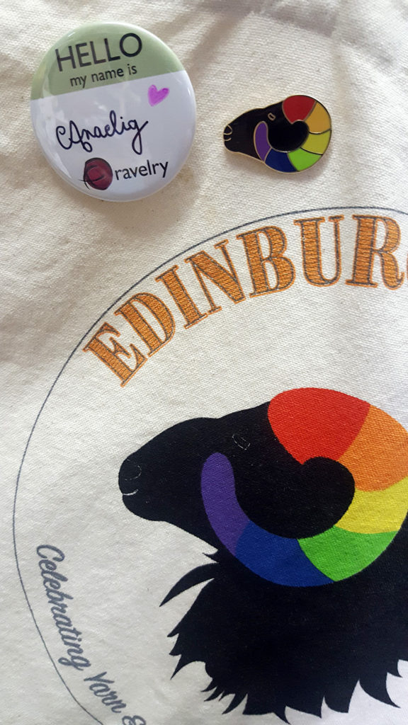 Mon badge Ravelry personnalisé avec mon pseudo et le merchandising badge et sac de l'Edinburgh Yarn Festival 2018, festival de laine et de tricot d'Édimbourg en Écosse.