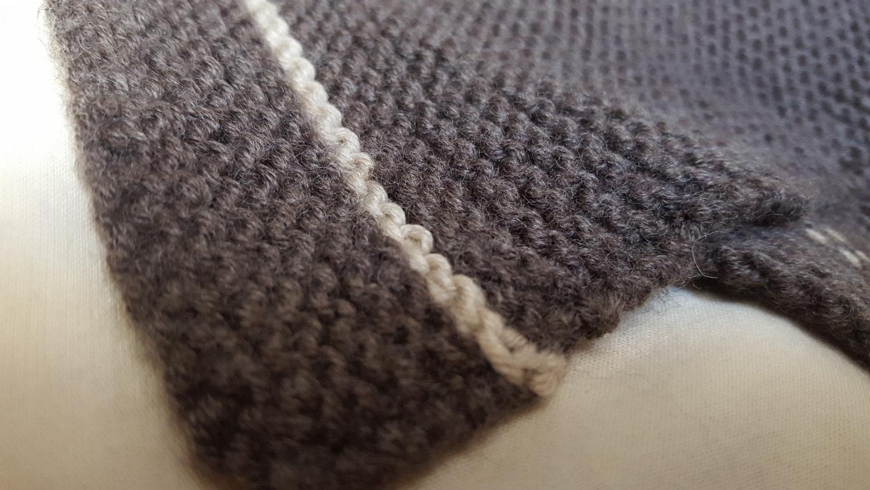 Détail de la couverture de mon chat tricotée en point mousse beige et marron.
