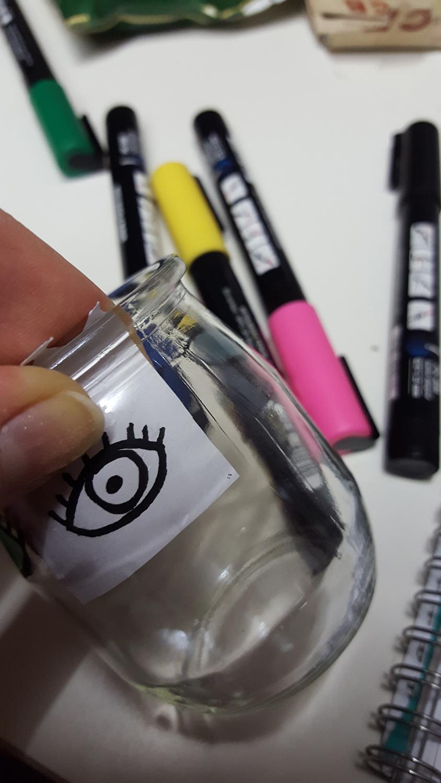 La technique pour avoir des motifs réguliers sur ses photophores décorés aux marqueurs Posca en mettant son dessin dans le pot de yaourt testée sur le photophore yeux en couleurs.