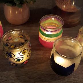 Plusieurs photophores décorés avec des marqueurs Posca éclairés avec une bougie pour créer une lumière douce et un éclairage tamisé.