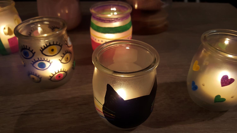 Les photophores décorés avec des marqueurs Posca éclairés avec une bougie pour créer une lumière douce et un éclairage tamisé.