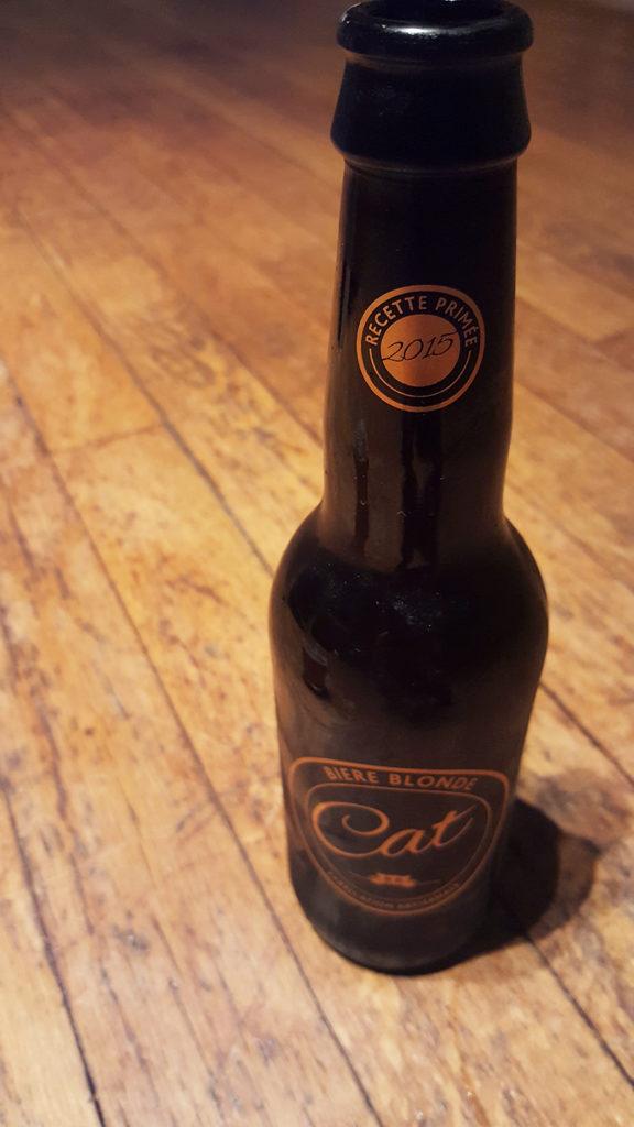 La bouteille de bière blonde artisanale Cat, dont la recette a été primée en 2015, et son super logo doré représentant un chat à côté.