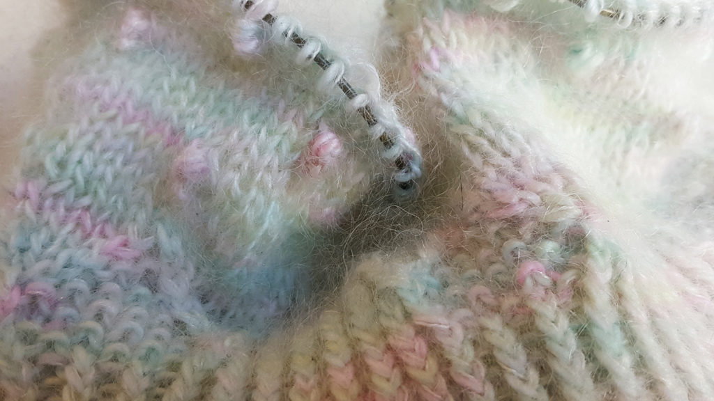 Gros plan sur le bonnet à noppes et côtes torses Kobuk de la créatrice Caitlin Hunter de Boyland Knitworks en cours de tricot à la main sur aiguilles circulaires par McLovin.