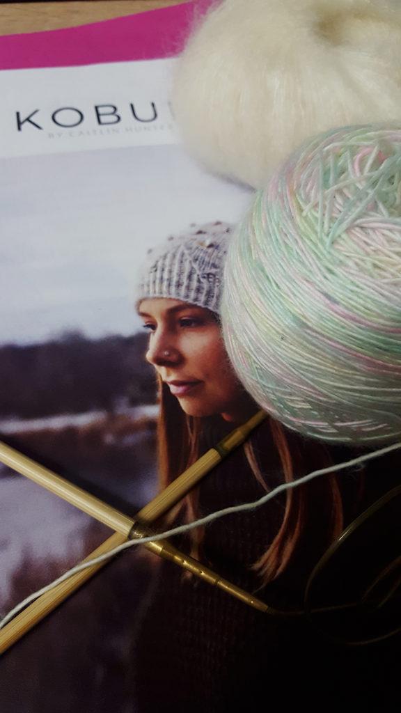 Les laines Skinny Single de Hedgehog Fibres coloris Down by the river et Mohair Luxe de Yarn blanche prêtes pour être tricotées sur les aiguilles circulaires Addi bambou en bonnet Kobuk de la créatrice Caitlin Hunter de Boyland Knitworks par McLovin.