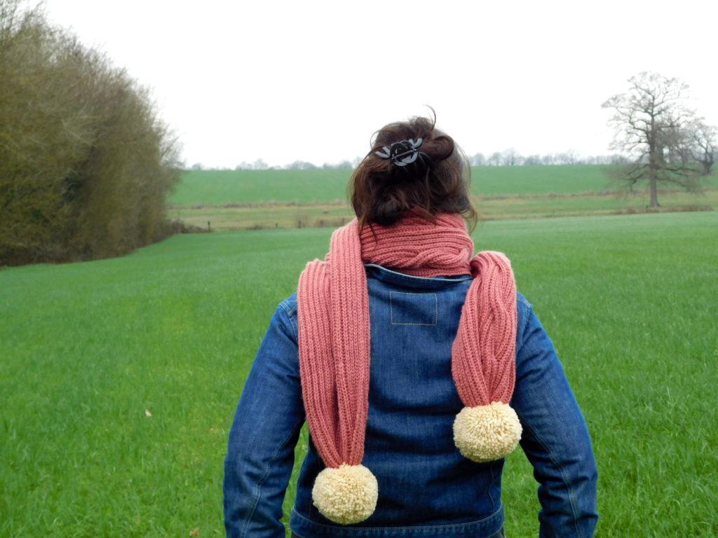 Ma grosse écharpe vieux rose avec ses énormes pompons crème tricotée main avec une torsade de côtes anglaises de dos.