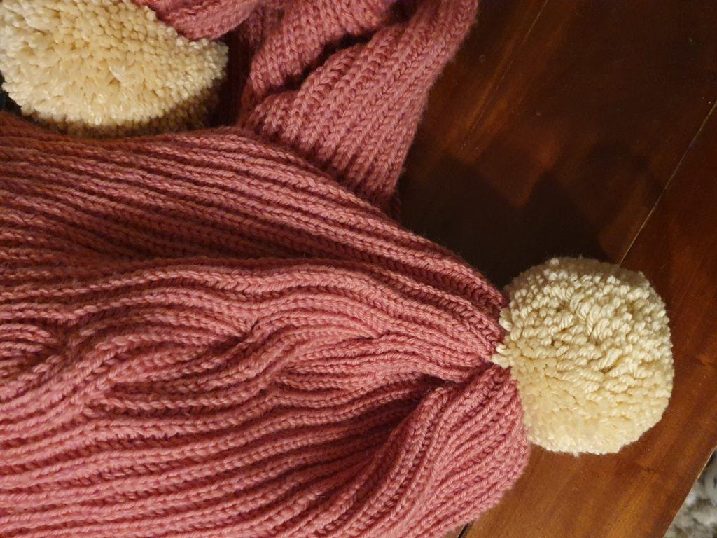 Ma grosse écharpe vieux rose avec ses énormes pompons crème tricotée main avec une torsade de côtes anglaises de haut.