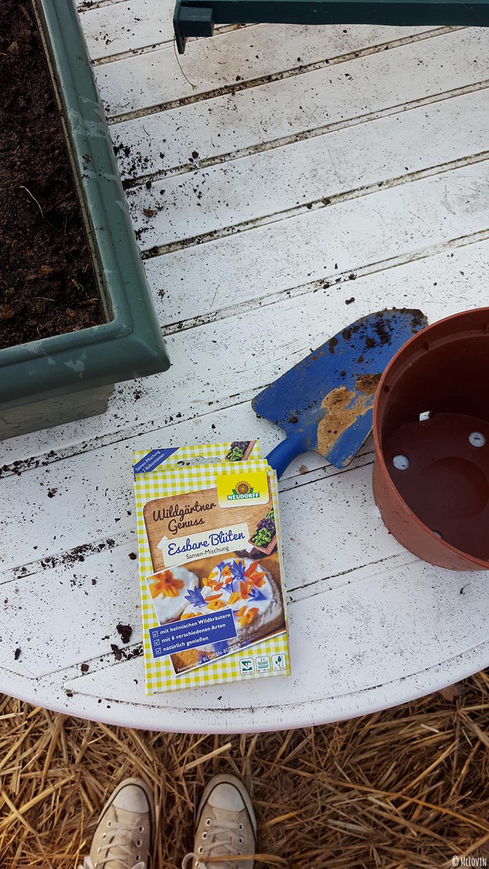 Le paquet de graines de fleurs comestibles Neudorff et le matériel pour les semer / planter dans la jardinière de la serre.