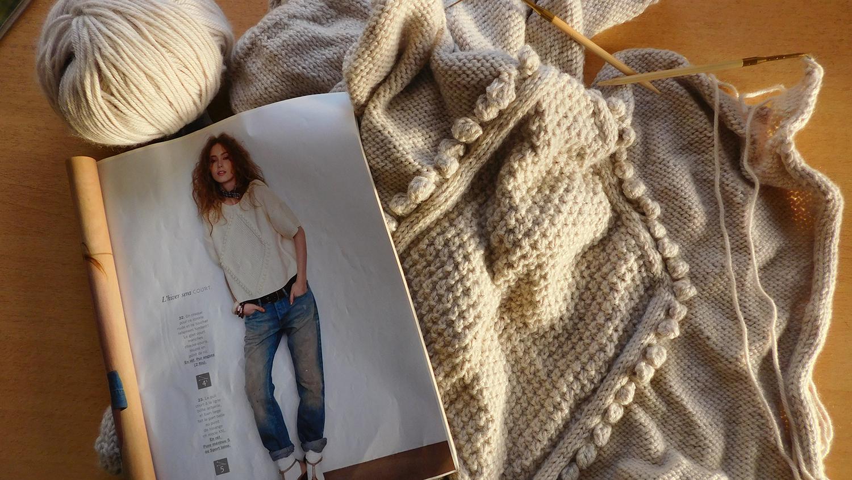Mon pull gris à noppes Phildar en cours de tricot avec le catalogue de modèles et la laine Katia Merino Aran.
